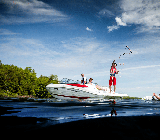 A person on a boat tosses a line to a water skier