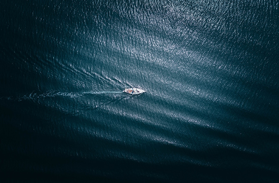 Aerial shot of lone sailboat on choppy water.