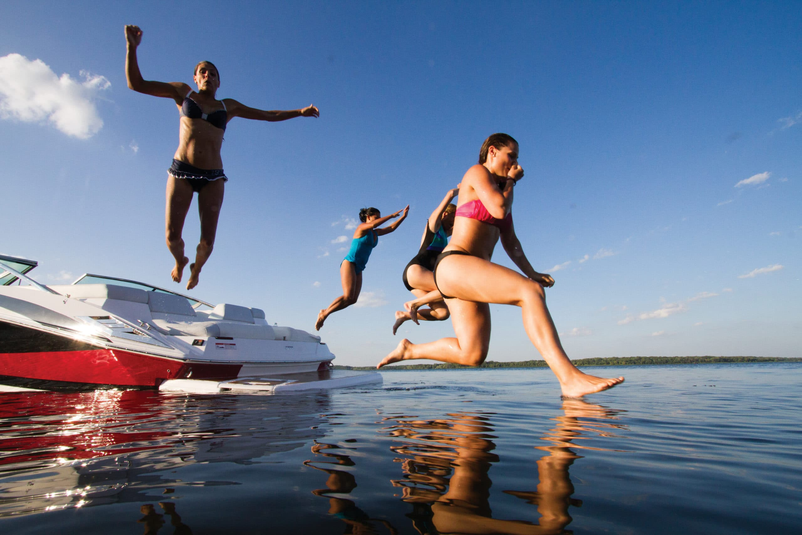 kids jumping into water from boat